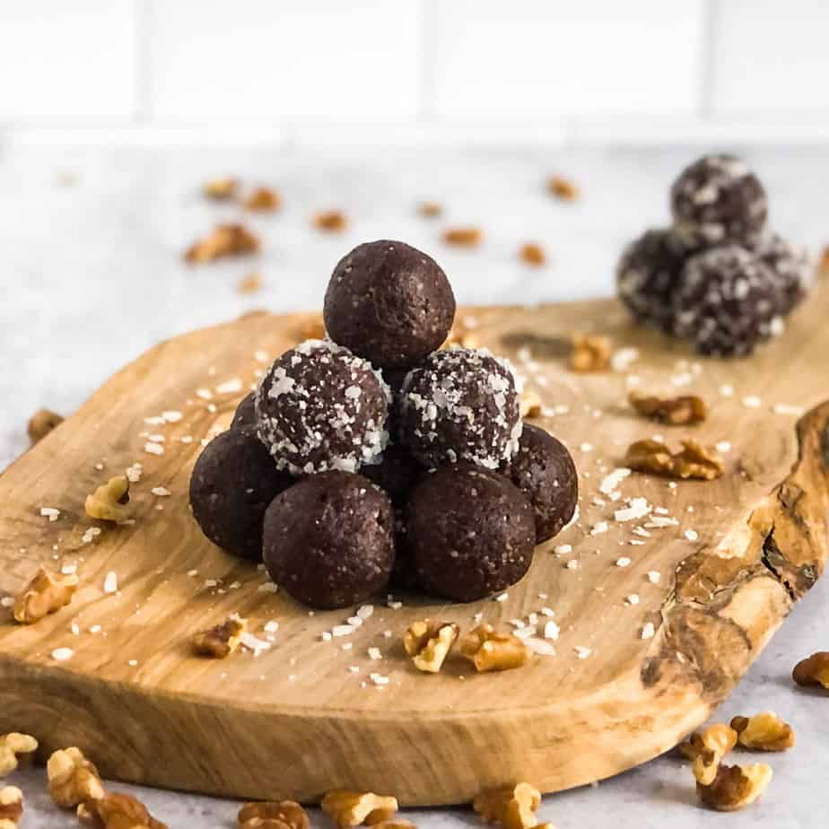 A pyramid of Walnut Date Balls on a wood cutting board with a second stack blurred in the background.