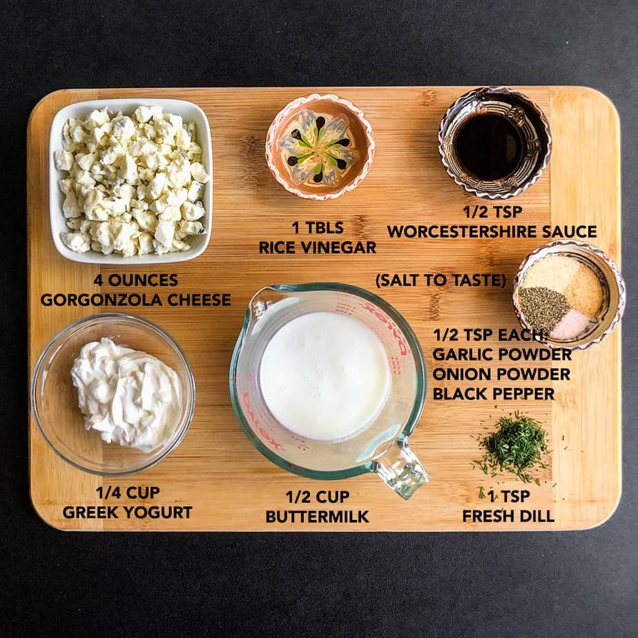 Ingredients for homemade dressing portioned in glass bowls on a wood cutting board.
