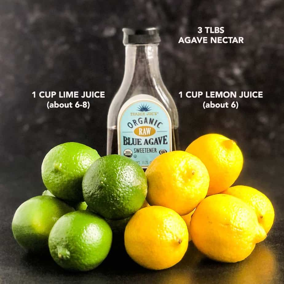 Bottle of agave nectar surrounded by lemons and limes.