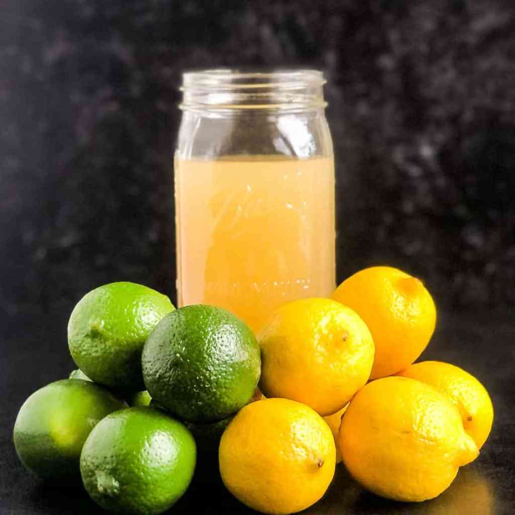 Quart jar of Homemade Sour Mix behind a stack of lemons and limes.