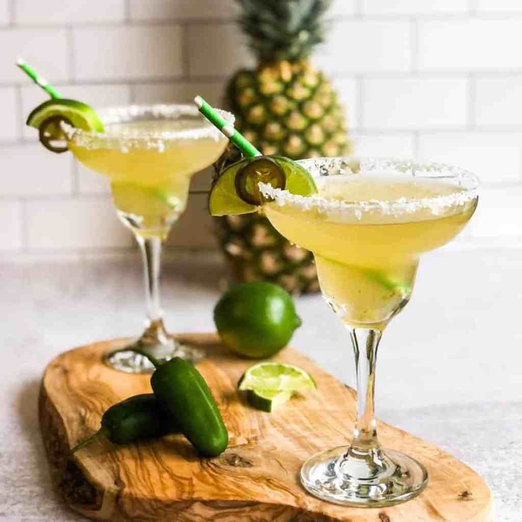 Two jalapeno margaritas on a wood cutting board with a pineapple blurred in the background.