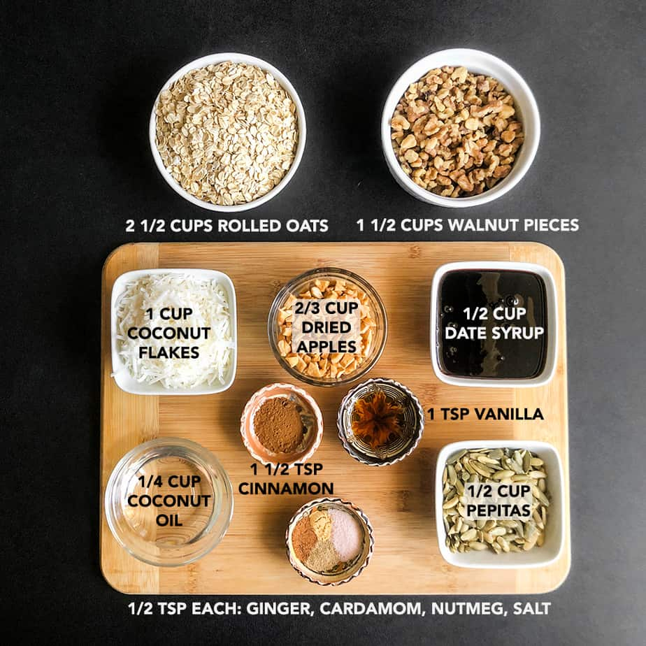 Ingredients for granola prepped and portioned on a wood cutting board.