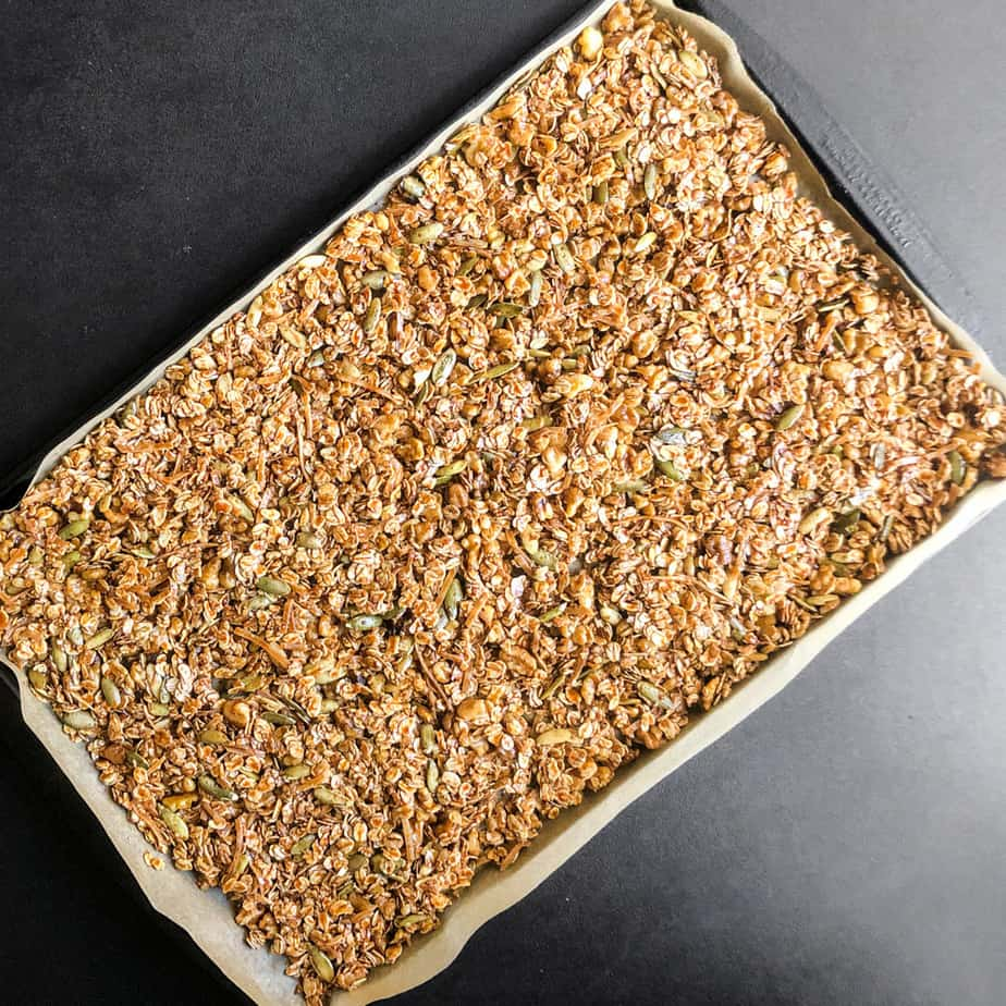 Granolo spread into a thin layer on a parchment lined sheet pan.