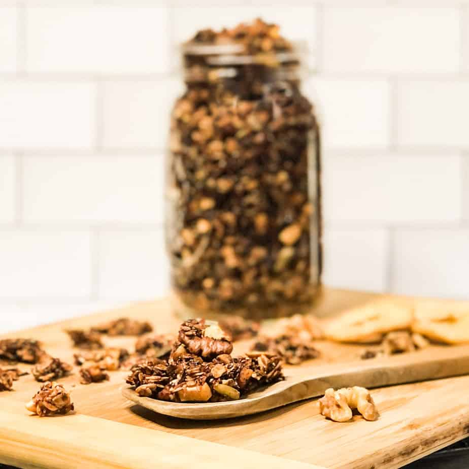 Granola on a wood spoon in front of a blurred jar of more granola.