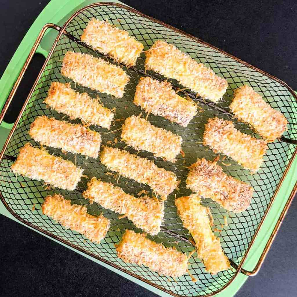 Cooked zucchini fries in air fryer basket on green cutting board.