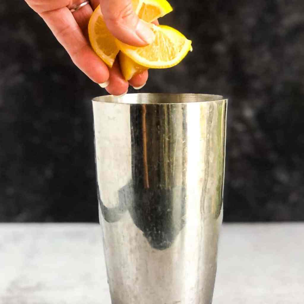 Hand adding lemons to a cocktail shaker.