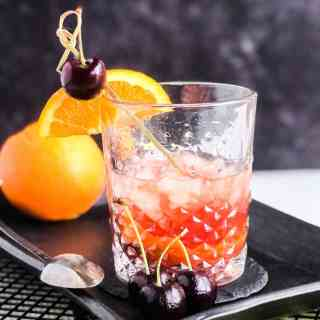 Maple Syrup Old Fashioned garnished with an orange slice and cherry on a black serving platter.