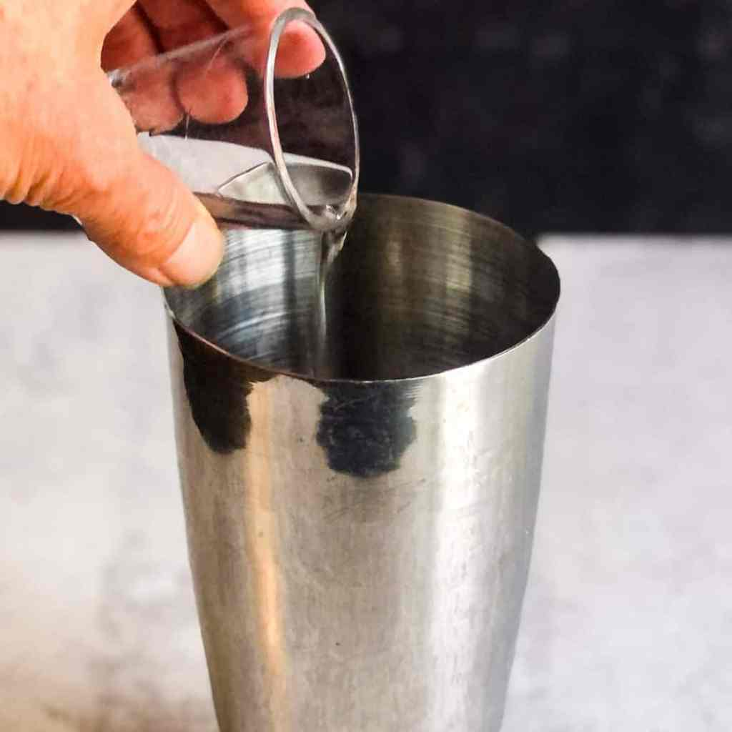 Hand pouring the vodka into a stainless steel tumbler.