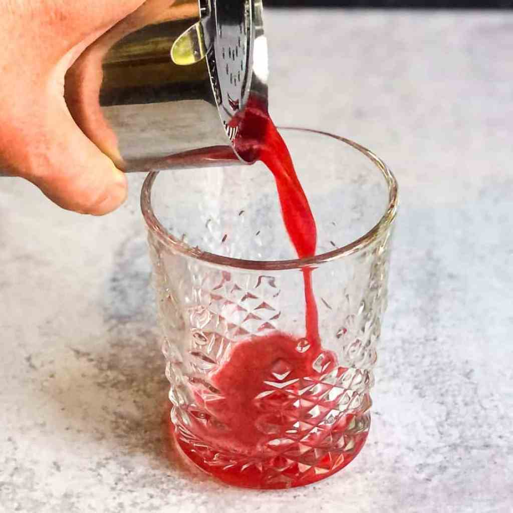 Hand pouring the Cherry Vodka Sour from a shaker tumbler into a rocks glass.