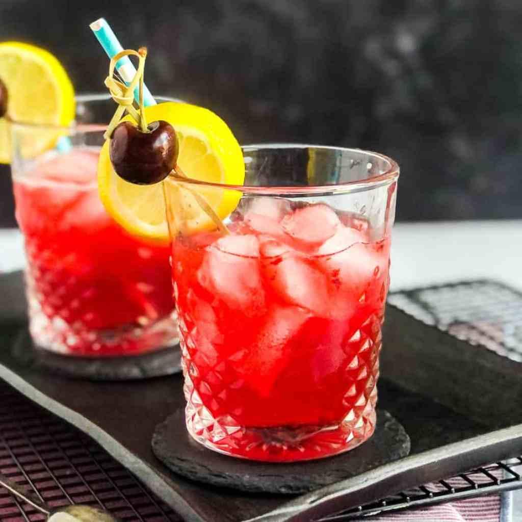 Two Cherry Vodka Sours on a black platter.