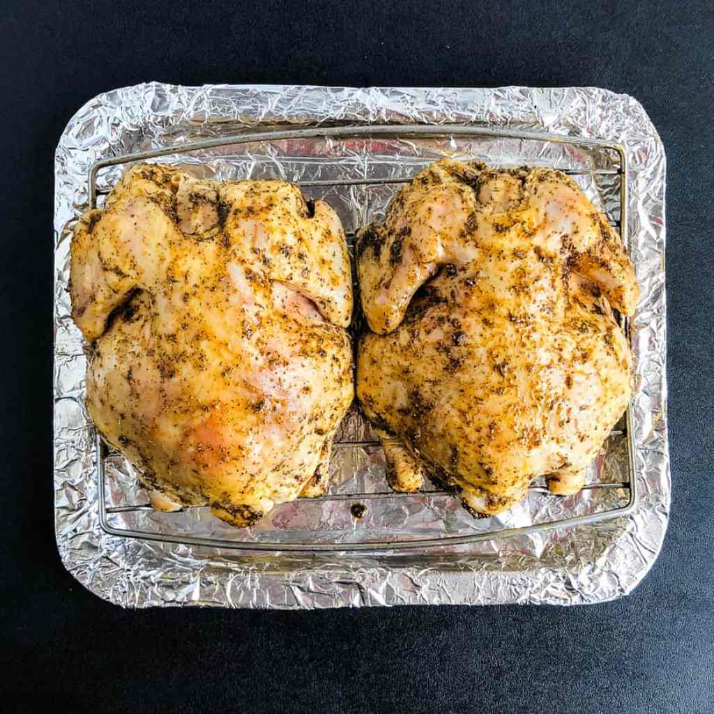 Cornish hens on a roasting rack with wet rub ready to go in air fryer.