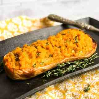 Mashed Butternut Squash inside it's skin on a black platter garnished with fresh thyme springs.