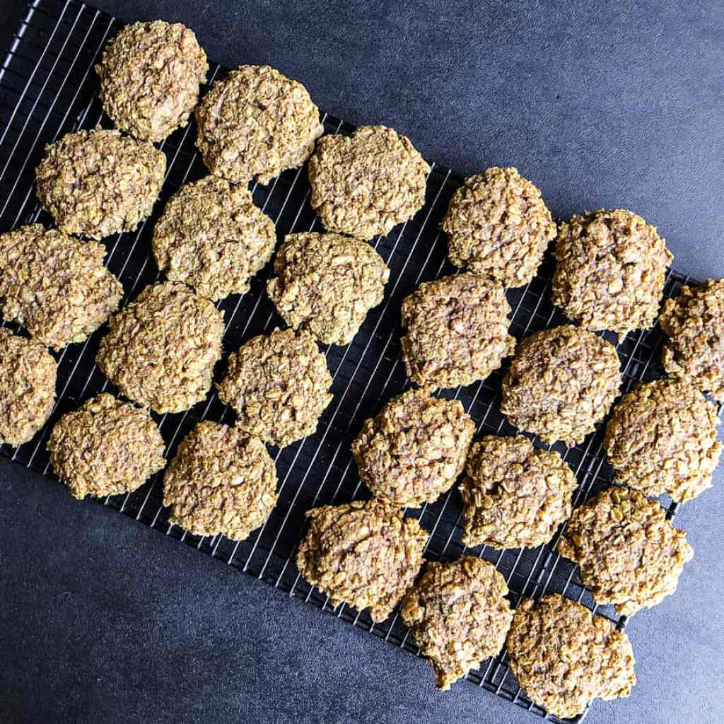 Cookies cooling on a baking rack on a black surface.