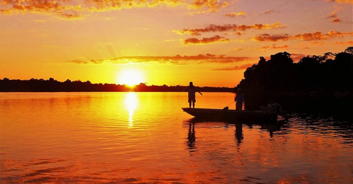 Anglers at sunset on a lake in the Amazon :: Inspired Spaces