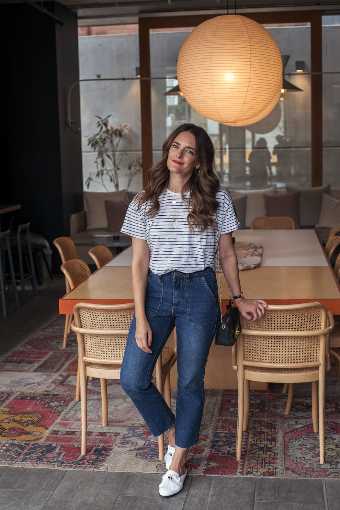 Cotton On denim edit worn by blogger Jenelle of Inspiring Wit. Wearing striped t-shirt, gold necklaces and indigo jeans at Alex Hotel Perth communal table with rattan chairs