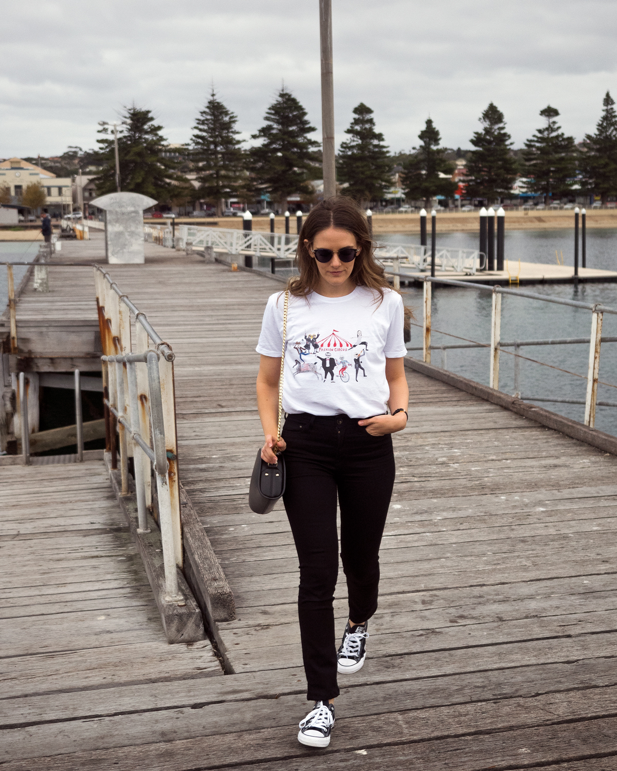 Oliver People's glasses, Unfortunate Portrait Fashion Circus t-shirt, Mavi black jeans, Black Converse sneakers, APC luna half moon bag winter outfit in Port Lincoln. Worn by Jenelle Witty fashion and travel blogger from Inspiring Wit