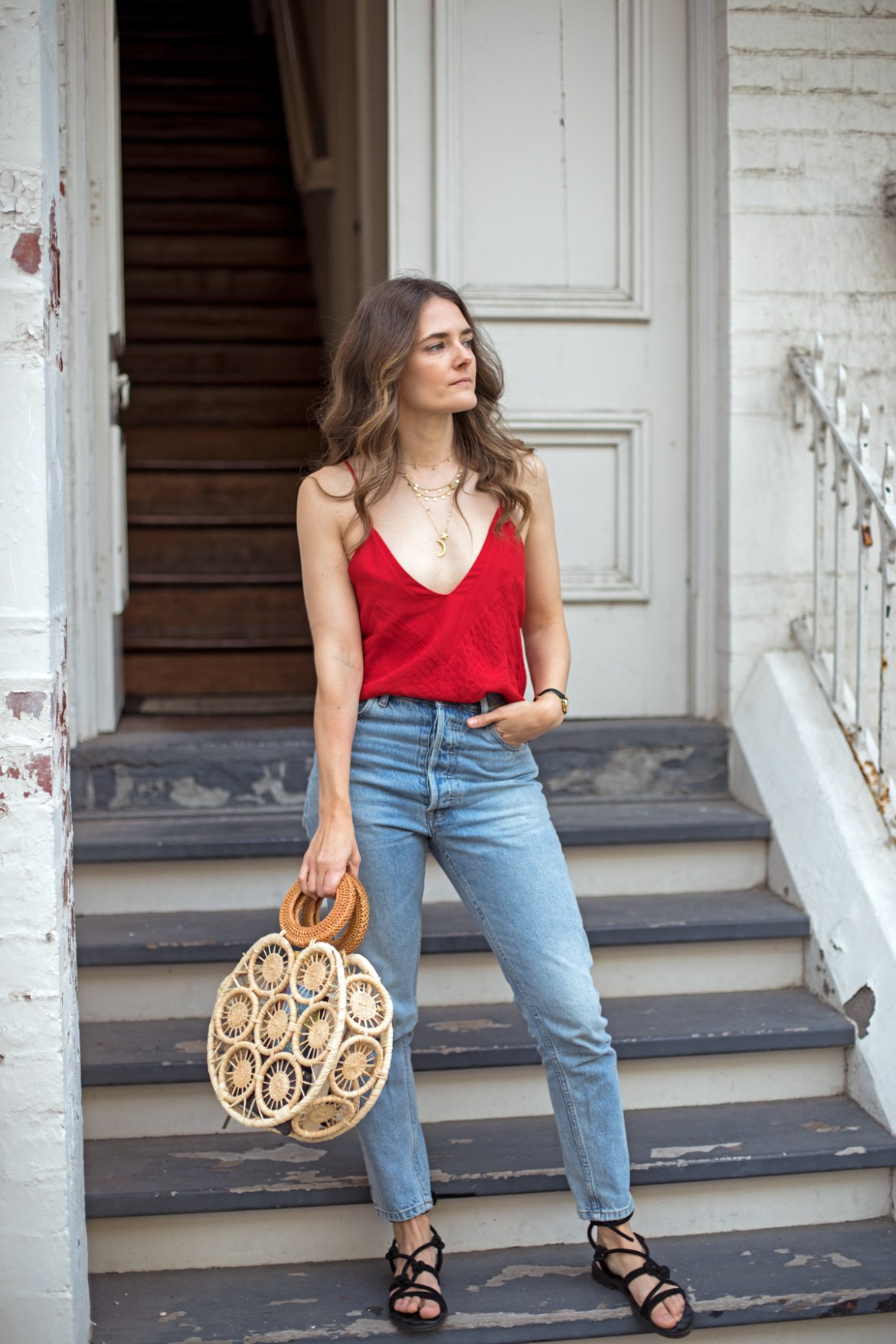 Anine Bing Sophie pintucked crepe de chine camisole in red worn with gold necklaces layered, Mavi mom jeans and Cult Gaia round straw bag by fashion blogger Jenelle Witty from Inspiring Wit