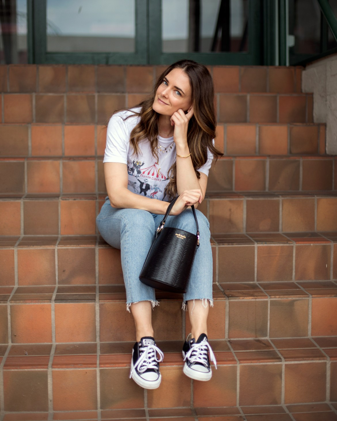 Meli Melo Santina bucket bag in black worn by fashion blogger Jenelle Witty from Inspiring Wit. With Unfortunate Portrait graphic tee, Levi's Wedgie jeans and Converse sneakers from Shopbop and Astley Clarke gold Mille Bangle