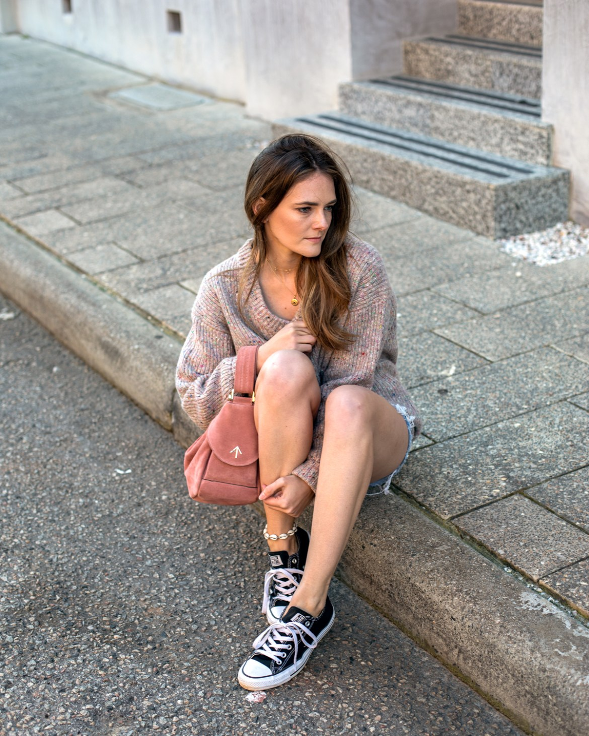 Jenelle from Inspiring Wit wearing pink Jac and Jack knit, Levi's shorts, Converse and Manu Atelier bag