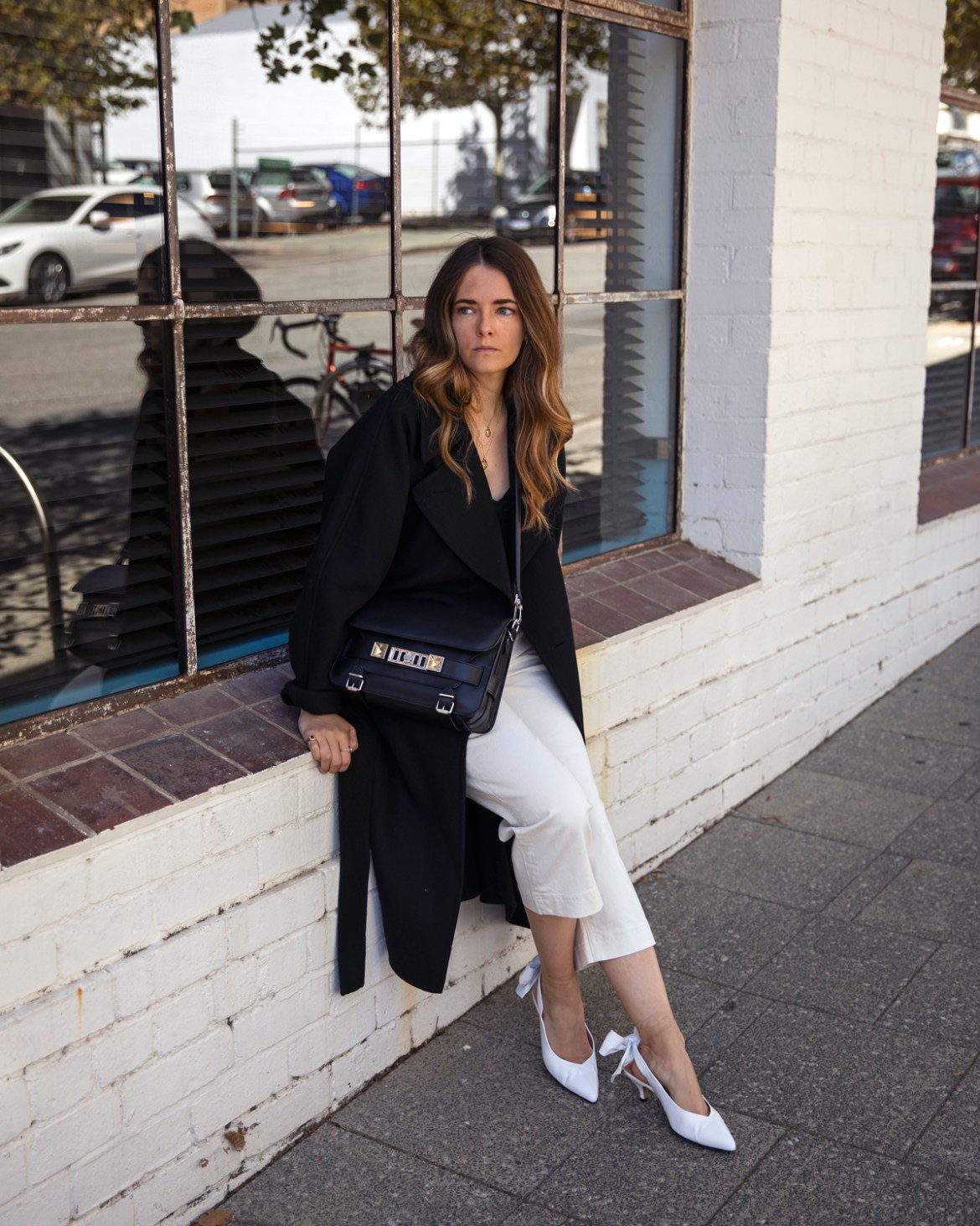 Uniqlo U black coat, Boden silk camisole, cropped jeans, Proenza Schouler PS11 bag and Ganni bow heels outfit worn by Inspiring Wit fashion blogger Jenelle