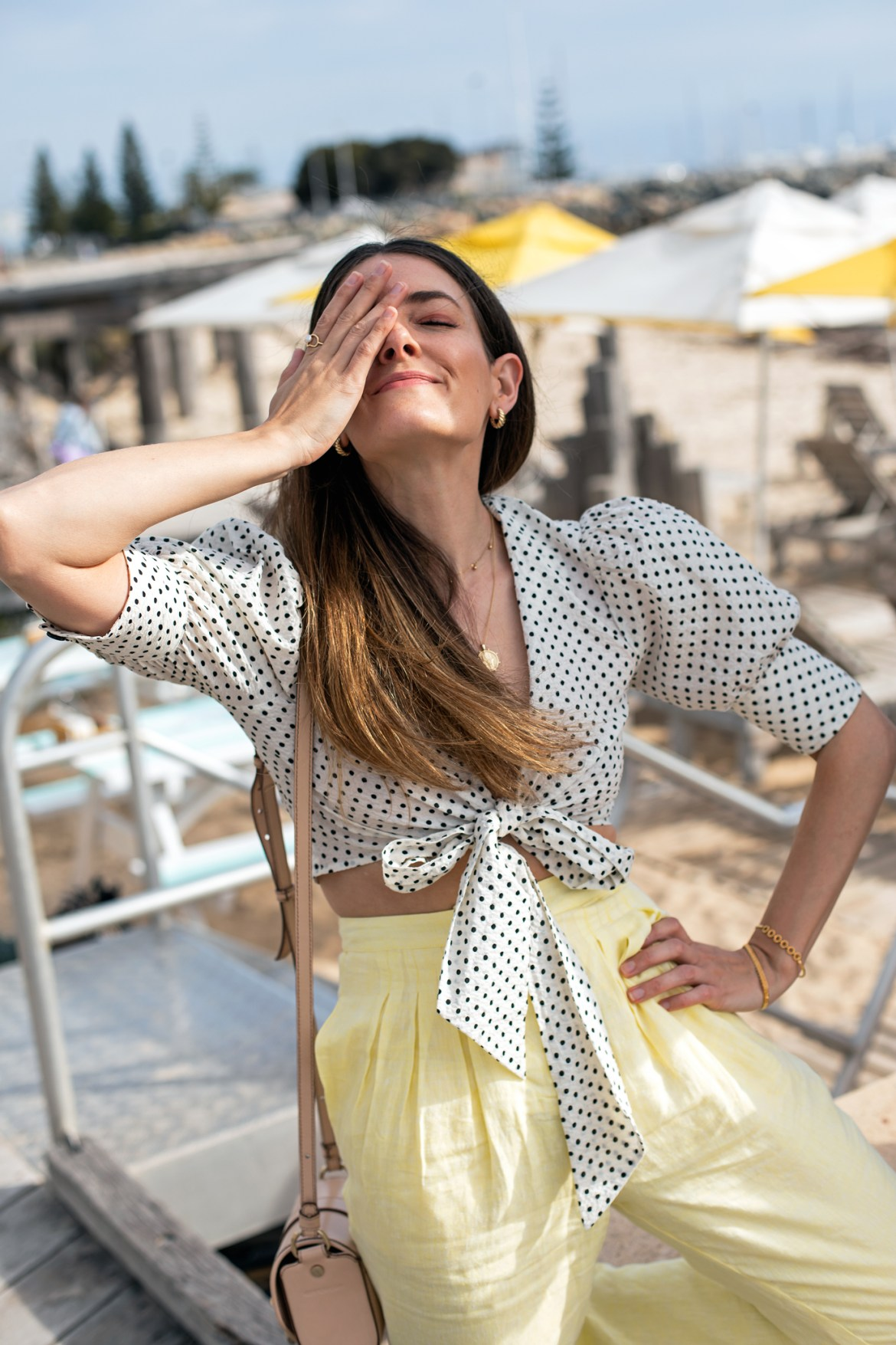 pastel yellow pants and a cute polka dot crop top outfit idea for your sunny vacation