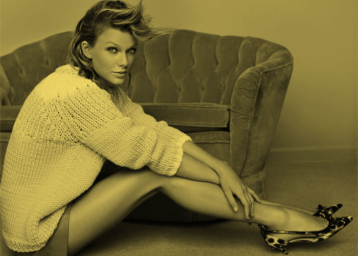 A seated Taylor Swift, pop star, shows off her slender, long legs.