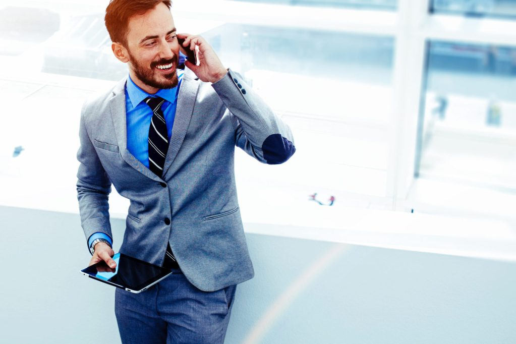Business in the cloud, man laughing on phone with tablet.