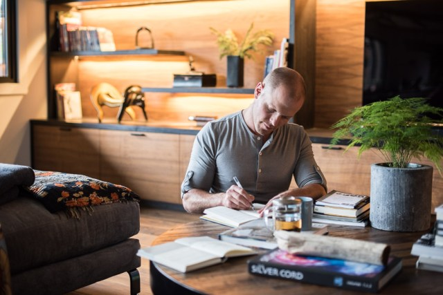 Tim Ferriss writing in a journal, surrounded by books at a table.