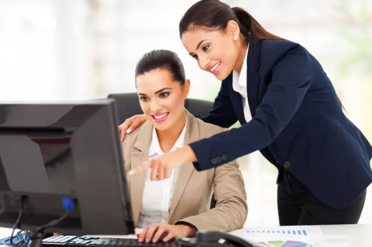 cheerful two business women working at the office on a computer