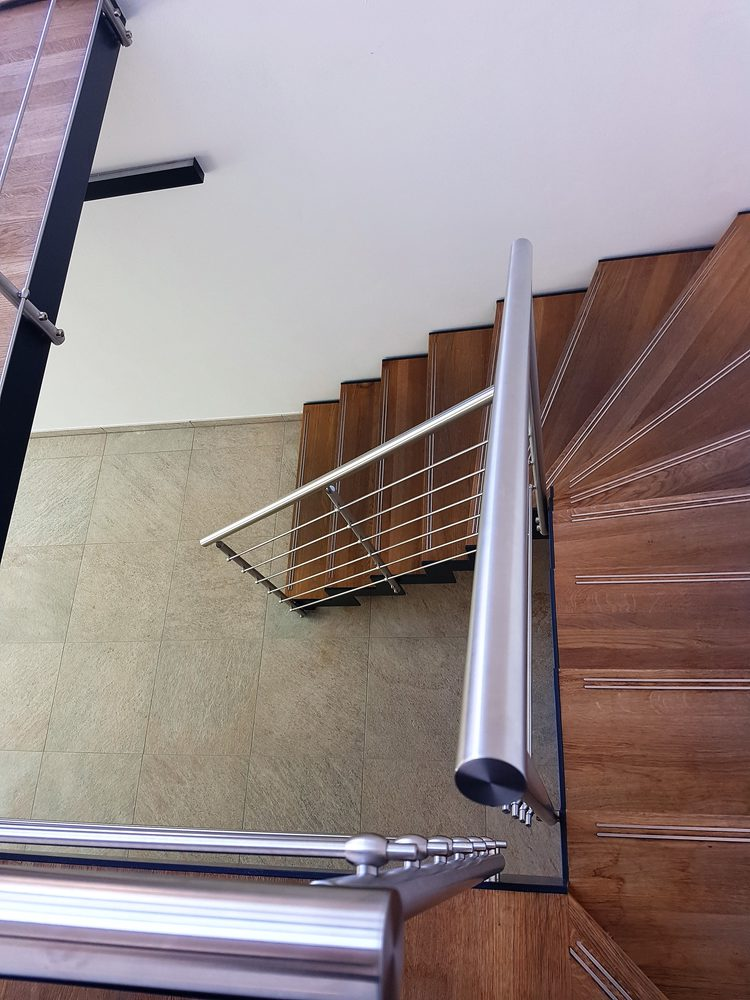 Dettaglio gradini in legno e ringhiera aperta in metallo per scala da interni