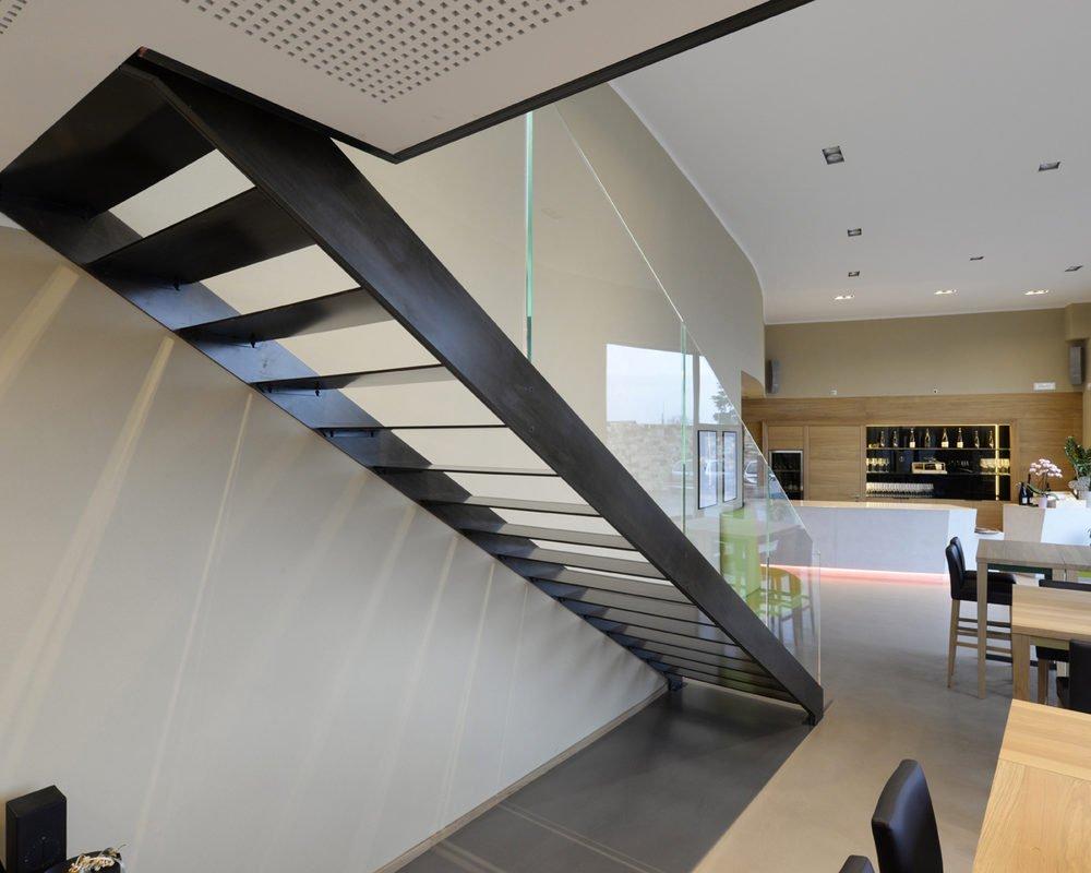 Scala di design a giorno, a rampa dritta, realizzata con doppio fascione in ferro brunito.