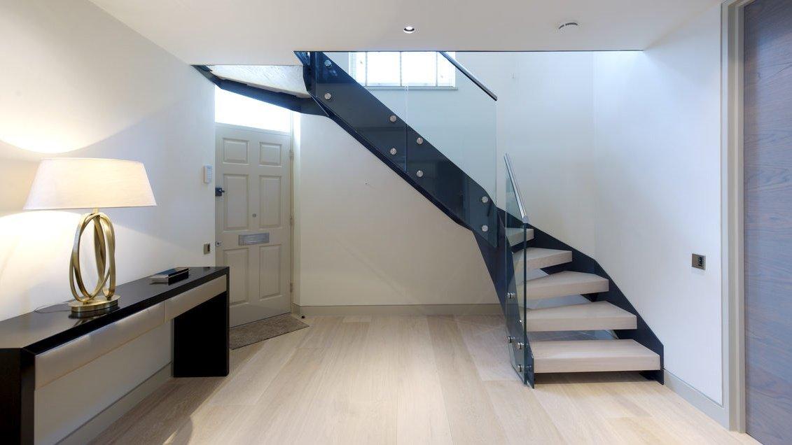 Scala di design per interni grigio antracite con pavimenti in rovere sbiancato a campione e lastre di vetro