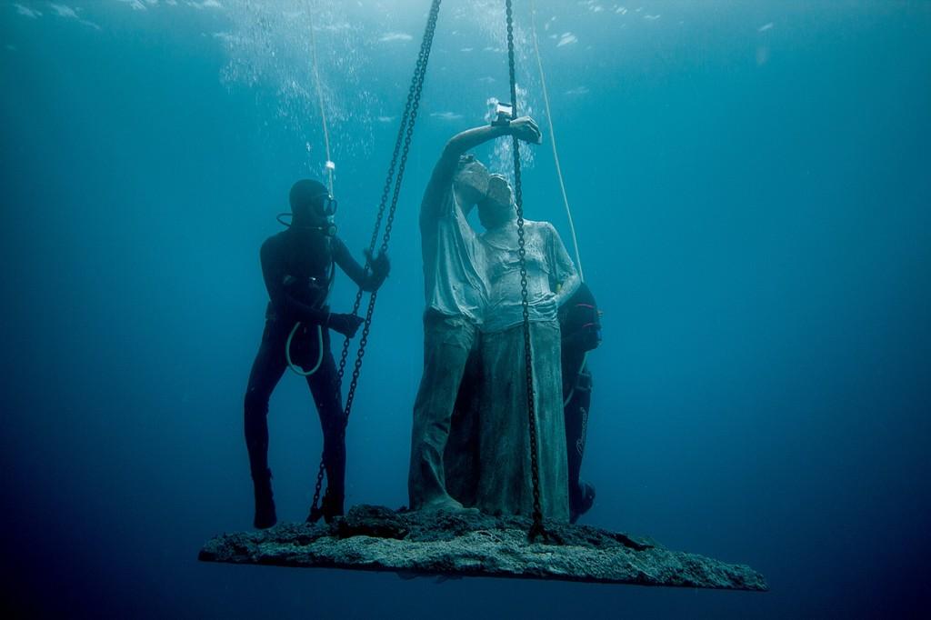 Escultura de figuras humanas haciéndose un selfie mientras los buzos la descienden al suelo marino.