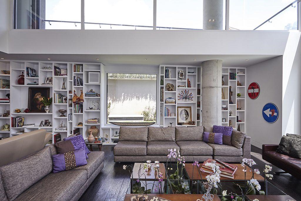 En la sala, de doble altura, los sofás tapizados con tela de Mariana Barriga con cojines de Mónica de Rhodes, juegan con la mesa de centro, compuesta por cubos de madera y peceras de vidrio con orquídeas. Fotografía: Gabriel Lugo.
