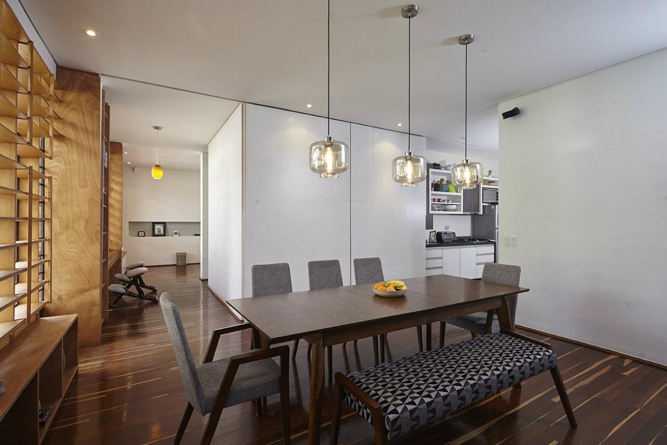 Los paneles corredizos blancos permiten ocultar o dejar a la vista la cocina. A la derecha se ve el corredor que conduce a la única alcoba. Fotografía: Luis Gabriel Lugo.