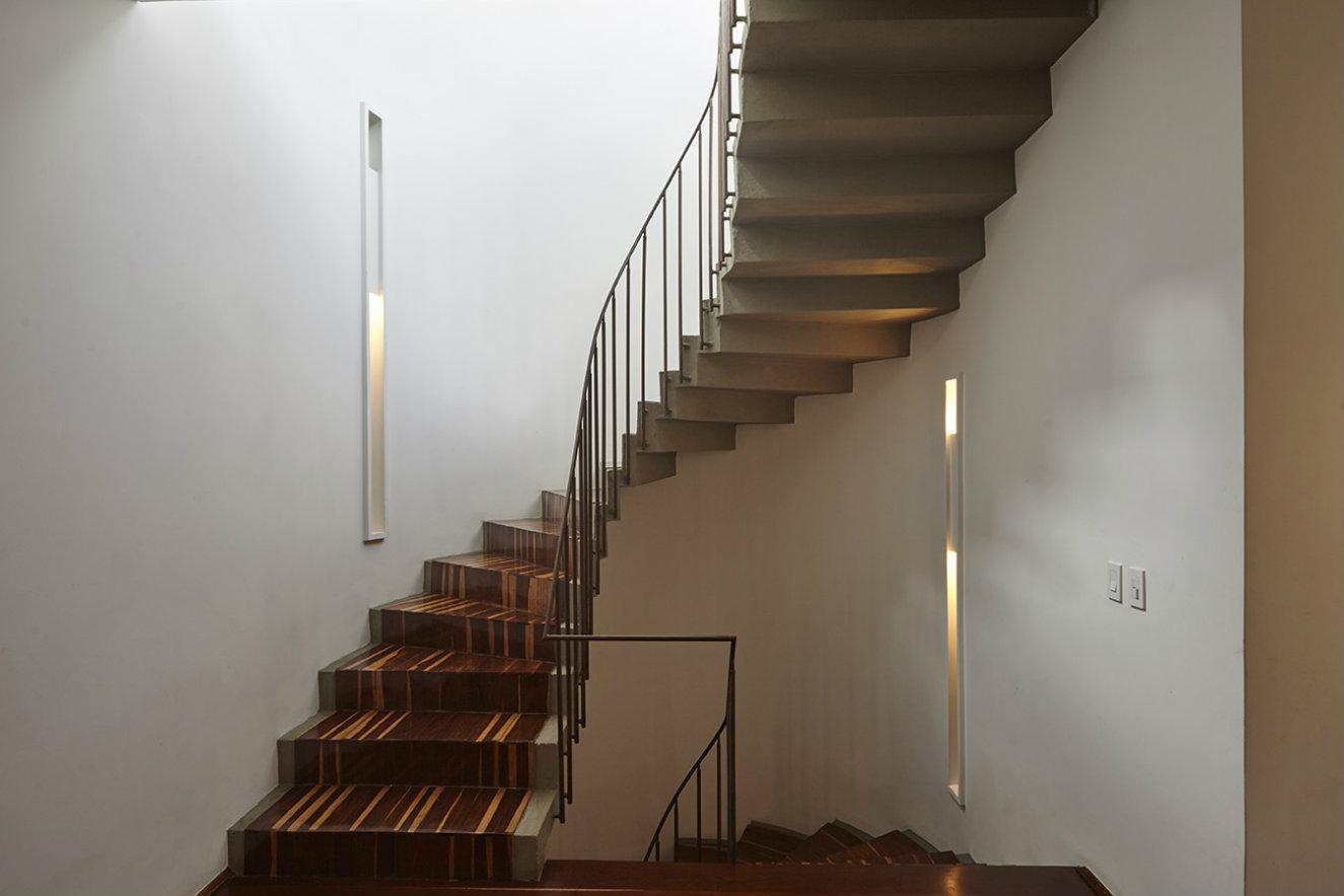 La escalera que conecta los tres pisos es la original, construida en 1957. Se destaca la iluminación empotrada en los nichos de las paredes. Fotografía: Luis Fernando Ramos.