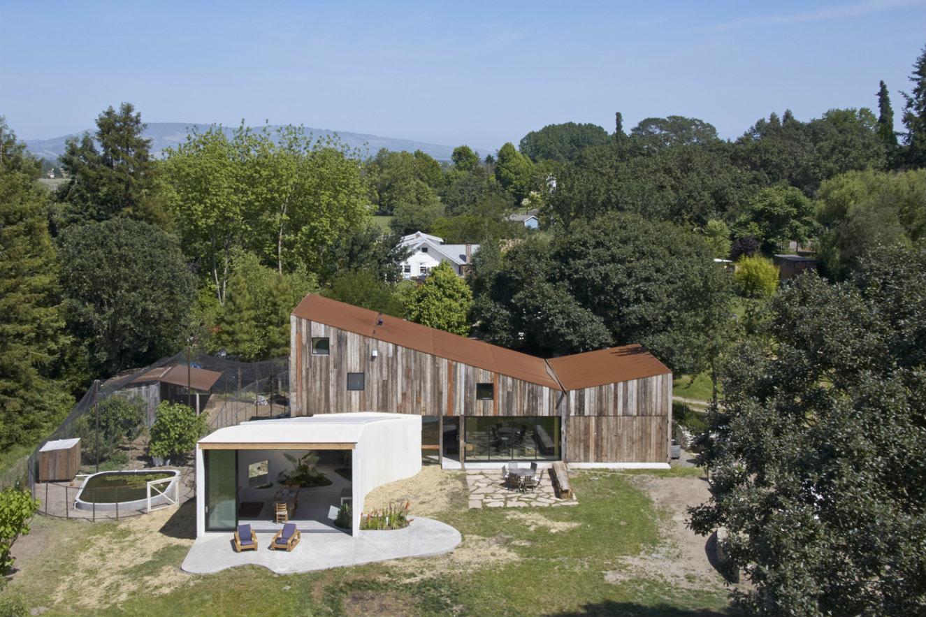 El estudio de la pareja sobresale por la fachada cubierta con listones de madera reciclada y el techo con acero oxidado. Fotografía: © Bruce Damonte.