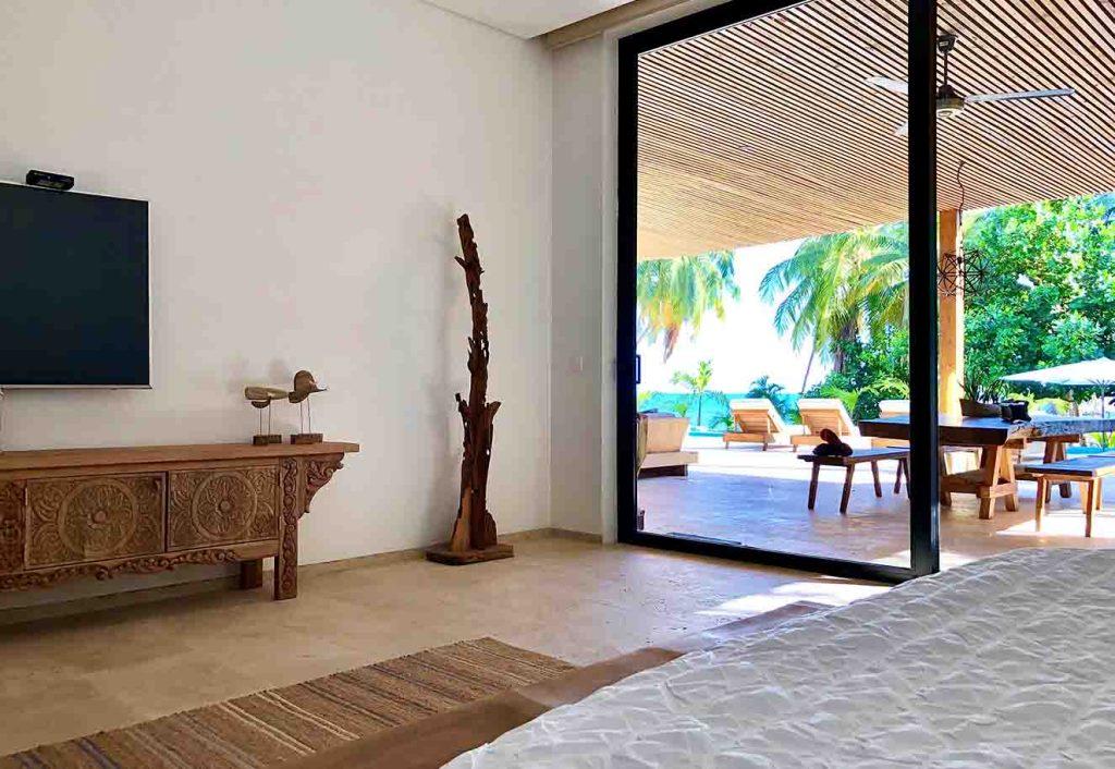 El dormitorio principal con vista al mar cuenta con salida a la terraza. Un tapete de fibras naturales, un mueble de madera tallada y abado r´sutico y un