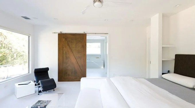 All-white-minimal-bedroom-with-a-lovely-barn-door-for-the-bath