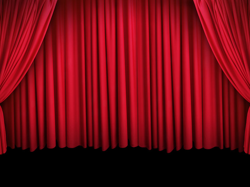 Image of a large stage with a red theatre curtain