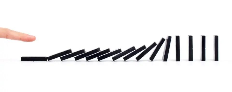 Un dedo empuja unas fichas de dominó en fila causando un efecto dominó en cadena