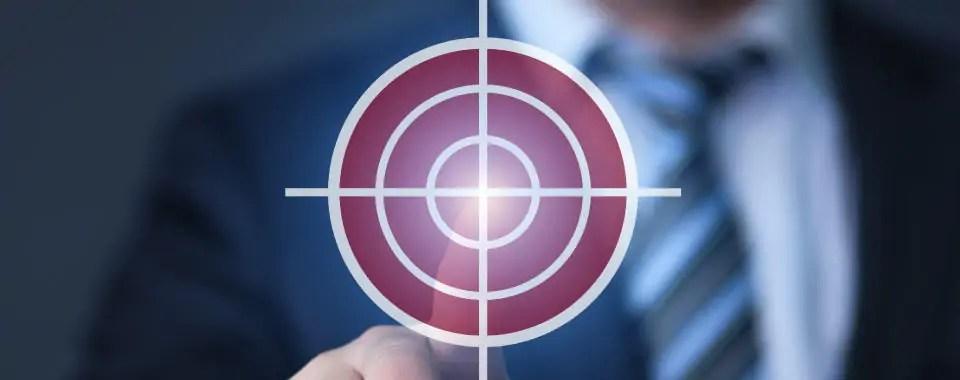 La mano de un ejecutivo toca la diana de un tiro al blanco para simbolizar quiénes son clientes de coaching