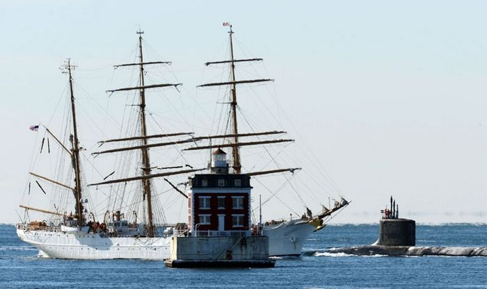 The United States Coast Guard Barque Eagle motors past New London Ledge Light as the U.S. Navy Virginia-class attack submarine USS California (SSN 781) passes southbound.