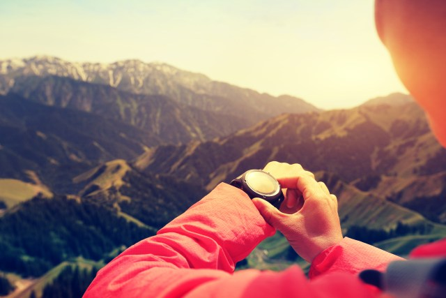 young woman hiker checking the altimeter on sports watch