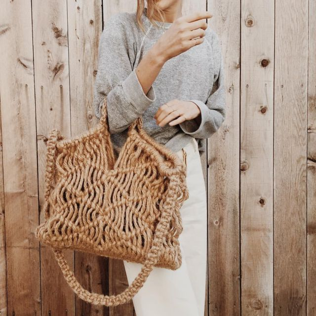 a macrame bag with a wooden handle