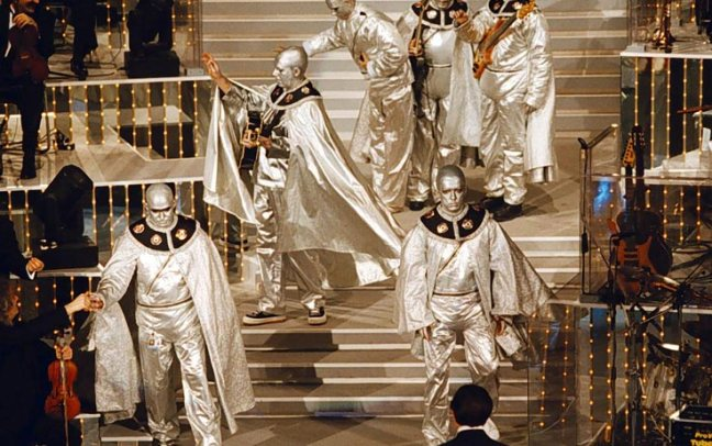 Nel 1996 gli Elio si esibiscono a Sanremo con 'La terra dei cachi': il brano arriverà secondo (da un'indagine successiva risulterà invece che fu la canzone più votata, confermando l'irregolarità della votazione, ma senza conseguenze sull'assegnazione), vincendo invece il premio della critica.
