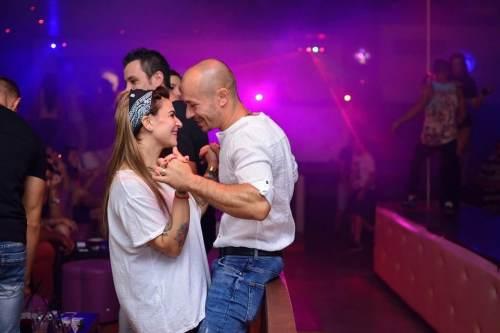 Par der danser med lilla lys i baggrunden
