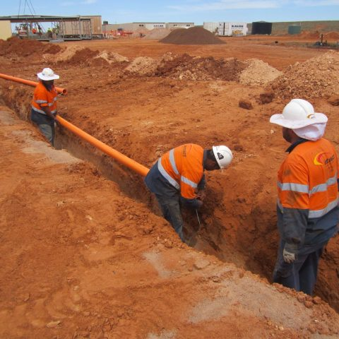 Three intract employees installing pipes at Carrapateena Exploration Camp Construction site