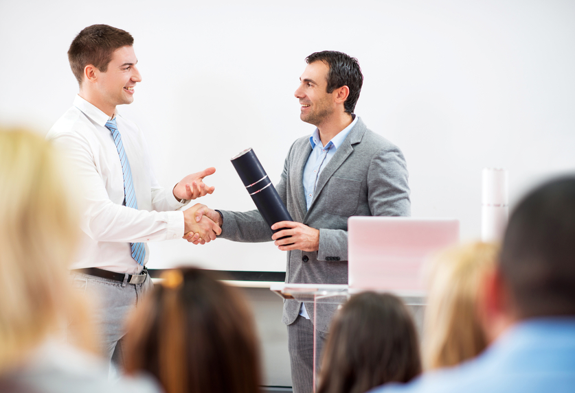 Group of people on a seminar. Focus is on businessman shaking hands with a teacher and receiving a diploma from a lecturer.