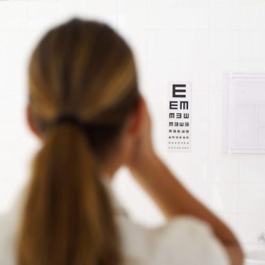Rear view of a woman looking at an eye chart